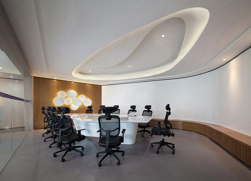 大会议室同样以细腻的象牙白作为主调,整体给人简约明净的感觉。类椭圆形的天花吊顶设计,既有凹面的视感,又有凸面的设计效果,十分巧妙。不规则的异形会议桌,与天花相映成趣。一组乳白的圆形状壁灯造型,如一颗颗耀眼明珠,散发出明亮的光辉,又像一个个饱含思想的原子,在不断交互碰撞,启发创客们的创意与灵感。墙边仿地台设计的座椅,有效地扩充了会议室的容纳空间,极富动感的线条也让空间更具韵律感。小会议室一面墙饰以世界地图,另一面墙则以色彩丰富的挂画作为装饰,利于与会人员发散思维,提高创造力。现代风格设计的三角形天花吊顶,是
