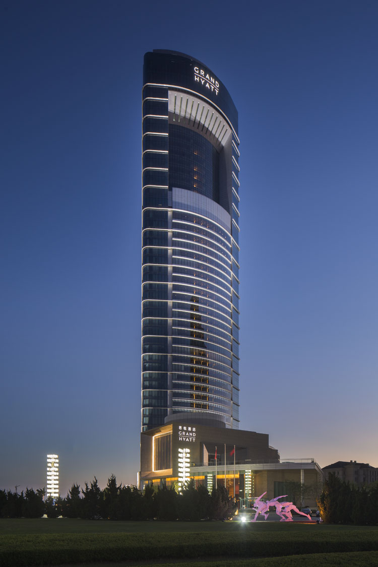 大连君悦酒店位于大连星海广场,地处海滨风景区,距离星海湾沙滩仅一步之遥,周边商业云集,交通十分便捷。酒店共包括28间套房,84间服务公寓,两个宴会厅,会议室,三个餐厅,一个水疗中心,一个室内游泳池和健身中心,以及225个停车位。 项目塔楼平面为三角形,旨在确保所有房间均可照射到南面阳光,并尽享延绵的海岸线景观。