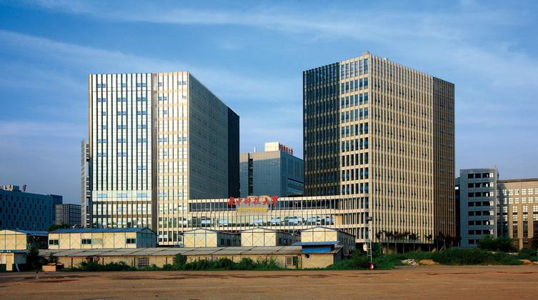 項目基地尊重虛擬大學園區原有規劃:保持北側、西側街面的延續性,在打造西側為形象昭示面的同時,考慮到西側未來規劃有超高層,減少主要功能空間的設置。讓中心公園延伸進來,與建筑直接接觸,使80%的辦公單元可以面向中心公園。南側塔樓身處中心公園最核心的位置,以一個充滿個性的CUBE來形成此區域的核心,滿足主要人流方向視線對景的需求。 建筑設計上,項目采用現代形式風格,立面樸實而富有趣味,且光潔、前衛、時尚。在建筑兩層高空間的基礎上設計豎向開窗,滿足辦公舒適性的同時,也使建筑造型本身成為本區