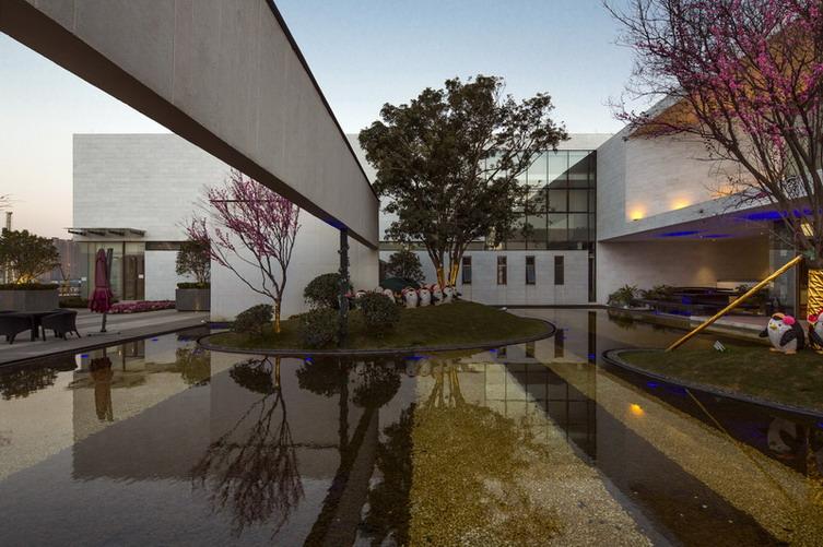 建筑设计采用现代建筑风格,极简的手法及纯粹的材质使之表达出简洁而又精致的感觉。建筑共分两层:一层为通透无框玻璃面,二层为黄洞石密封拼接;整体简洁、细节精致、虚实对比强烈,整个建筑犹如漂浮于空中,影影绰绰的水面更是赋予无限遐想。院墙采用片墙互相架空穿插的手法,使内部景观外露但不显张扬,以现代的手法展现东方含蓄富有内涵的美学特色。